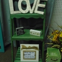 """Love"" Letters $2.00 Green Washed Three Step Wooden Shelving $12.00 ""Mr. & Mrs."" Small Cube Sign $.50 ""Every Love Story Is Beautiful..."" Small Cube Sign $.50 ""Please Sign Our Guest Book"" Burlap Bow Sign $2.00 Green, Blue, & Yellow Drawers $5.00"